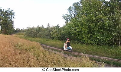 A girl riding a scooter on a country road
