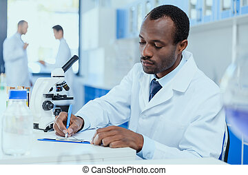 African american scientist in white coat taking notes while...