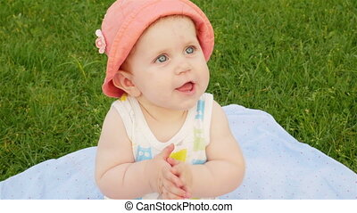 girl smiles and claps - Baby girl sits on a green lawn in a...