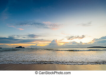 Beautiful sea waves pour into the sandy beach during sunset