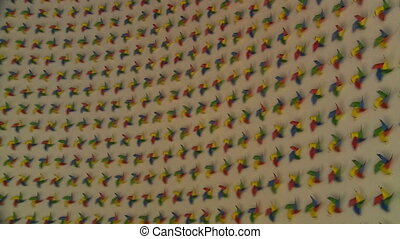 Rainbow spinning pinwheels spin on white wall. Handheld zoom...