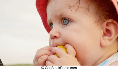 Cute little baby is looking away and is wearing a red hat....