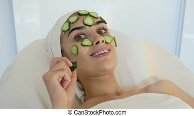 young and smiling women with cucumber mask at the beauty...