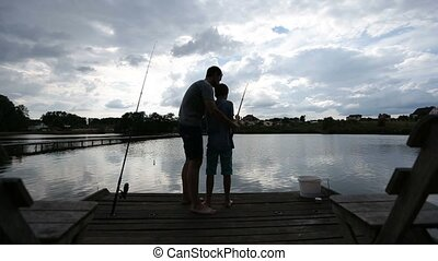 Teenage boy learning to fish with fishing rod - Attentive...