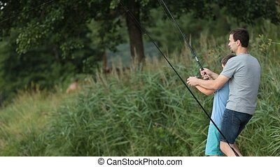 Excited son and father catching fish at pond - Side view of...