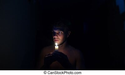 A man walks in the dark the house with a candle in her...