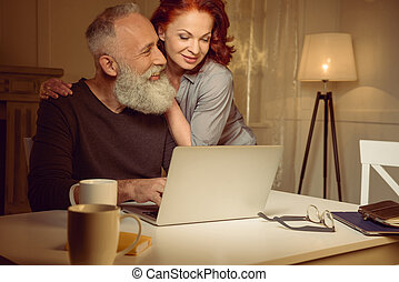 embracing middle aged couple sitting near laptop at home