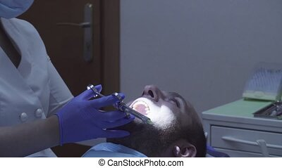 Dentist making the patient an anesthetizing injection -...