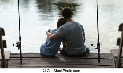 Affectionate father embracing son as they fish - Back view...