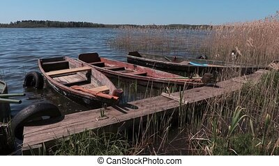 Old wooden fishing boats floating near the lake footbridge