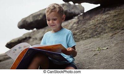 Boy in the mountains reading a book
