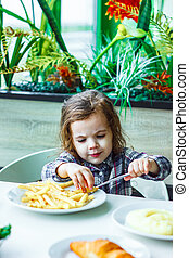 Kid girl in a restaurant eating fast food.