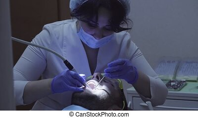 Dentist drilling tooth in dental clinic - Woman dentist...