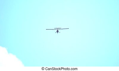 Small propeller plane flying in the sky, telephoto lens slow...