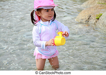 Japanese girl playing with water with watering pot (2 years...