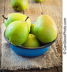 green pear in a metal bowl on a wooden table toning