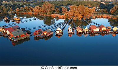 Flying over fishing houses line on the lake shore, Hungary.