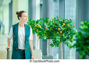 Young woman with baggage in international airport walking with her luggage. Airline passenger in an airport lounge waiting for flight aircraft