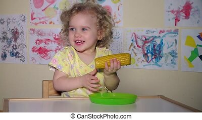 Young funny girl eating a boiled corn sitting by table at home