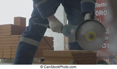 Worker cutting bricks. Brick cut with circular saw or grinder