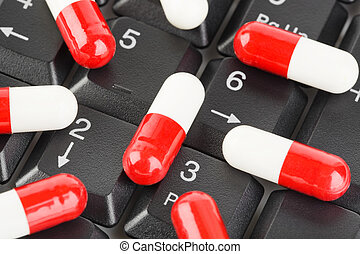 Pills on computer keyboard - concept technology background