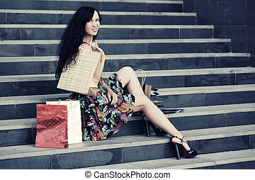 Happy young fashion woman with shopping bags on the mall...