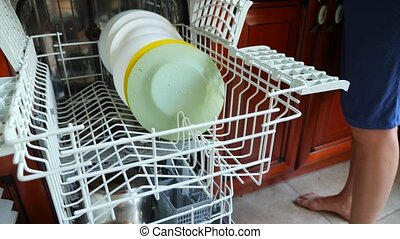 A woman is putting a plate on a shelf in a dishwasher....