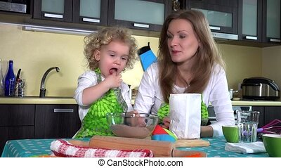 Little girl mother helper taste chocolate cake flour and mix it with spoon