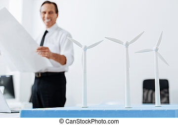 Cheerful engineer smiling while looking at wind turbines -...