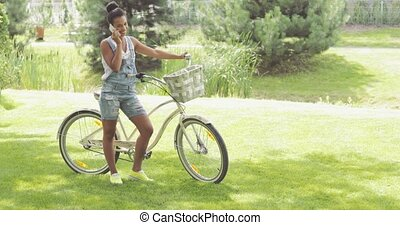 Young cyclist talking phone in park - Confident young girl...