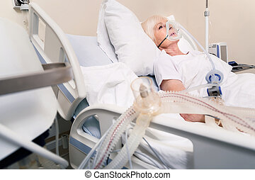 Feeble elderly woman breathing with artificial respirating unit