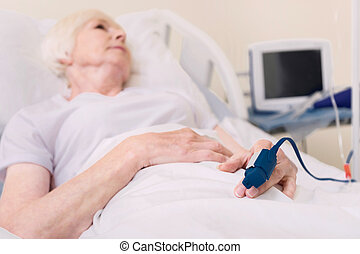 Elderly ailing woman wearing special device on her finger -...