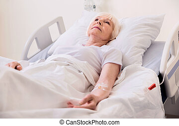 Vulnerable ill senior lady being treated in hospital -...