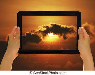 Woman hands holding tablet pc taking photo in nature