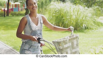 Content young girl with bicycle - Pretty young woman in...