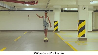 Girl skateboarding on parking - Young ethnic woman in denim...