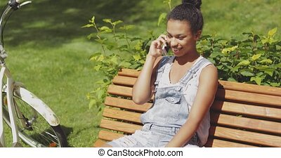 Cheerful woman talking smartphone in park - Young laughing...