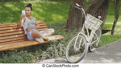 Cheerful model taking selfie in park - Young woman sitting...
