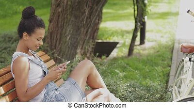Content girl using smartphone in park - Side view of young...