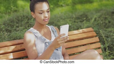 Model taking selfie on bench - Content young ethnic girl in...