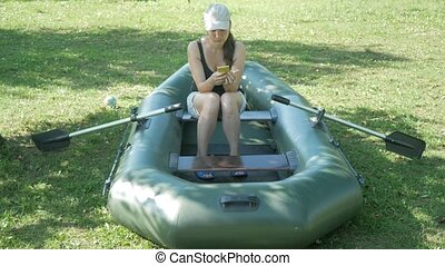 A pretty woman sits in an inflatable boat near the house and...