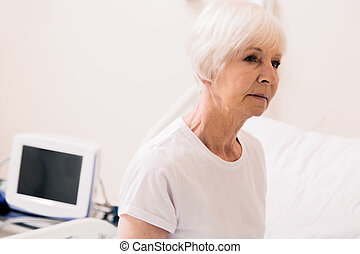 Charming vulnerable aged woman sitting up in hospital bed -...