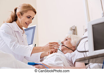 Neat competent woman putting an oxygen mask on her patient