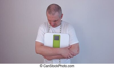 Worried man with measure tape and digital scale