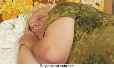 Senior man sleeps at home on a pillow. Gray hair and a light pillow under his head. The concept of rest