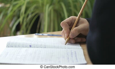 Student writes text in exercise book using pencil - Student...