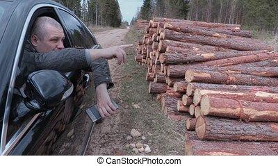 Lumberjack sitting in car near log pile and talking