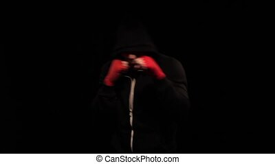 Boxer Throwing Punches in the dark gym