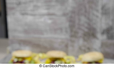 Zoom in from out of focus on delicious home made burgers next to French fries lying on wooden background