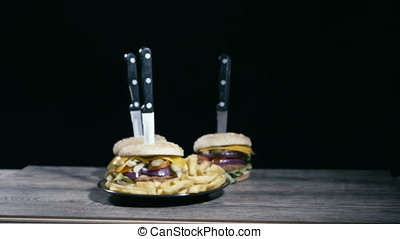 Zoom in on hamburger with fries on wooden table over black background